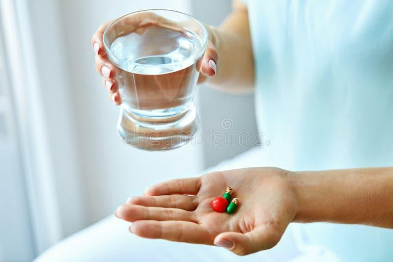 医学 拿着维生素和药片的女性手 胳膊关心健康查出滞后 免版税库存图片