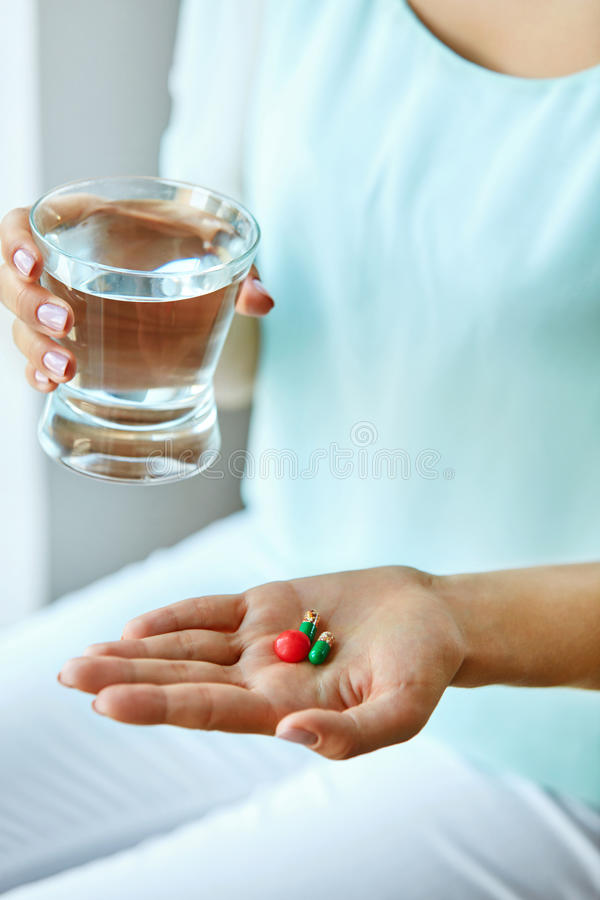 医学 拿着维生素和药片的女性手 胳膊关心健康查出滞后 免版税库存照片
