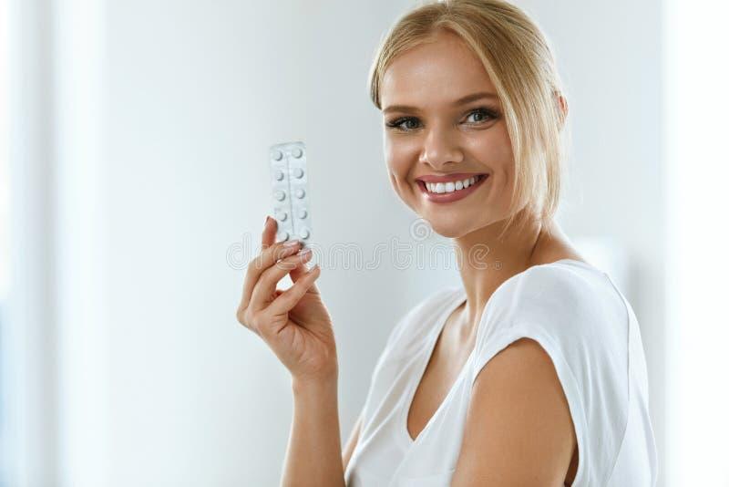 医学 握有药片的美丽的微笑的妇女水泡 库存图片