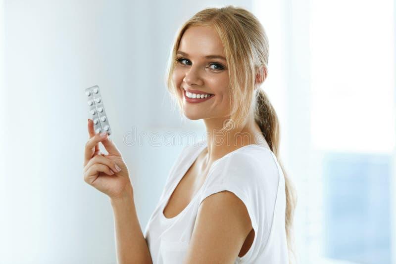 医学 握有药片的美丽的微笑的妇女水泡 图库摄影