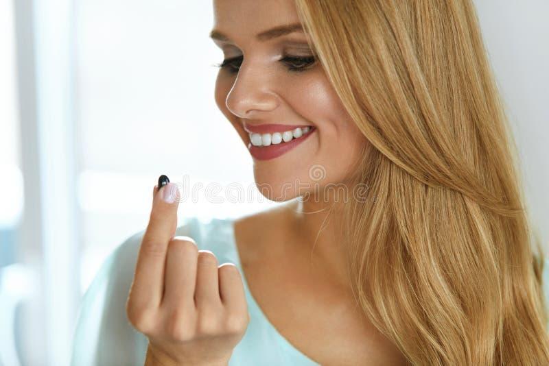 医学 采取疗程药片的美丽的微笑的妇女 免版税库存图片