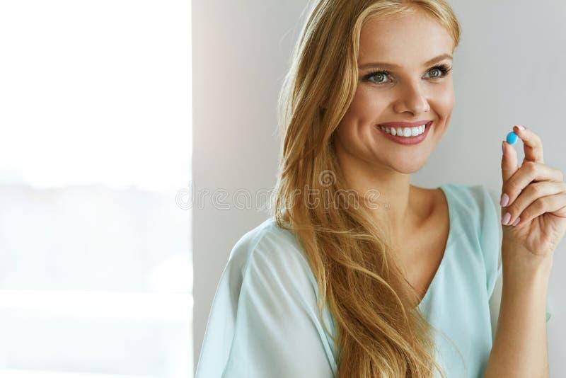 医学 采取疗程药片的美丽的微笑的妇女 库存照片