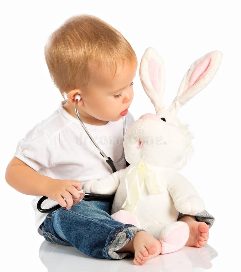 婴孩充当医生玩具小兔和听诊器 免版税图库摄影