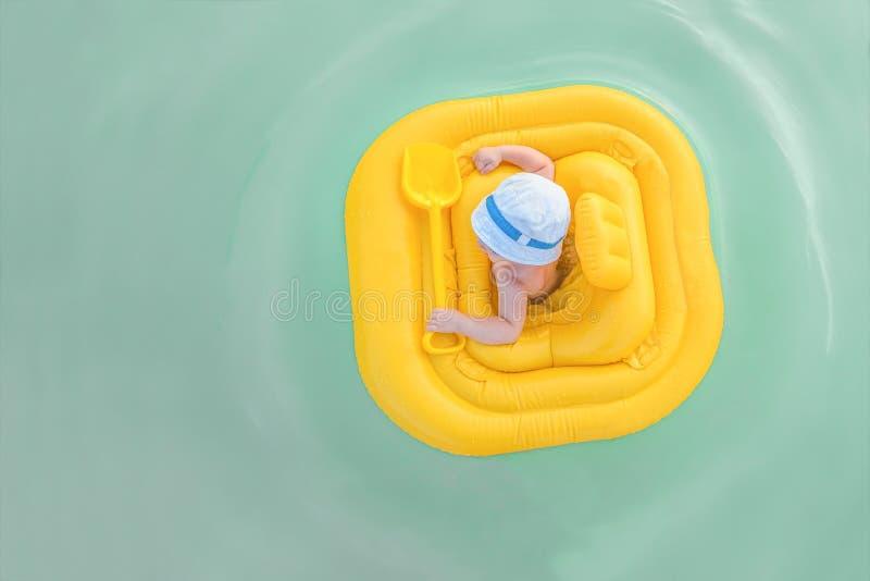 婴孩在一艘黄色可膨胀的木筏漂浮 与拷贝空间的背景 图库摄影