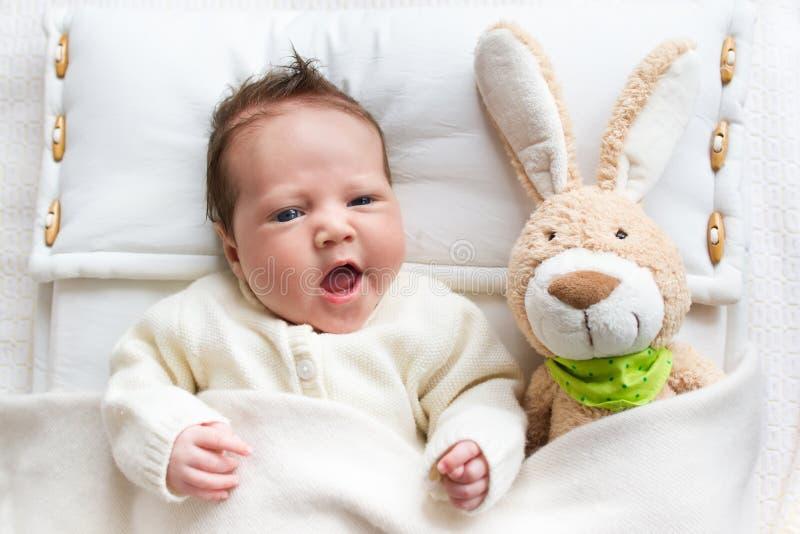 婴孩在与兔宝宝玩具的床上 免版税库存照片