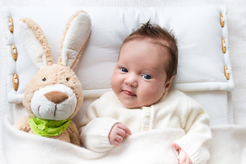 婴孩在与兔宝宝玩具的床上 库存图片