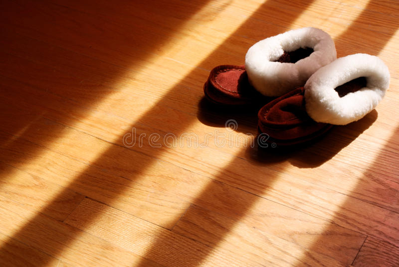 婴孩在硬木地板上的冬天拖鞋 库存照片