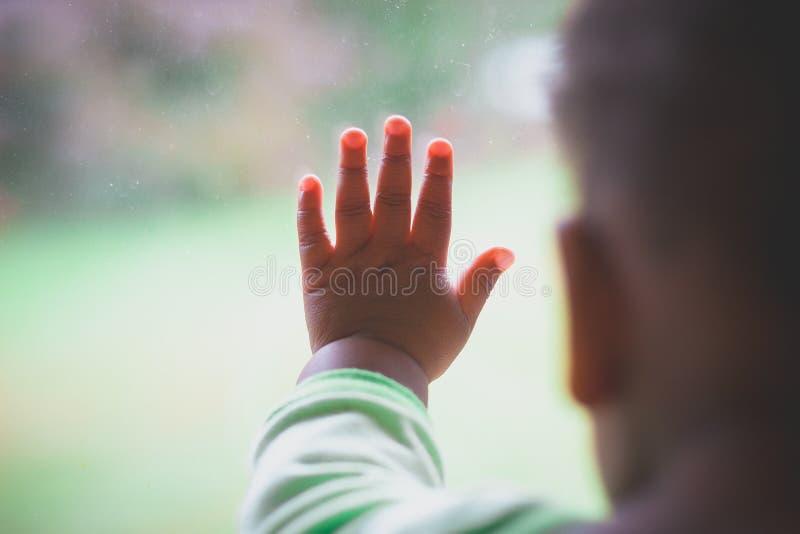 婴孩在窗口的` s手指 库存图片