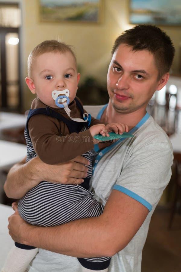 婴孩坐他的父亲的胳膊。 免版税库存照片