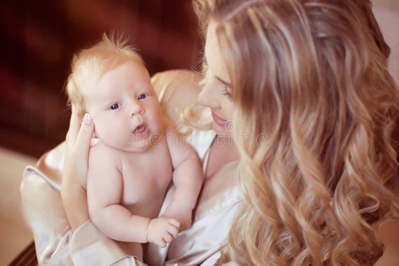 婴孩她的藏品母亲新出生的年轻人 使用与新出生的妈妈 免版税图库摄影