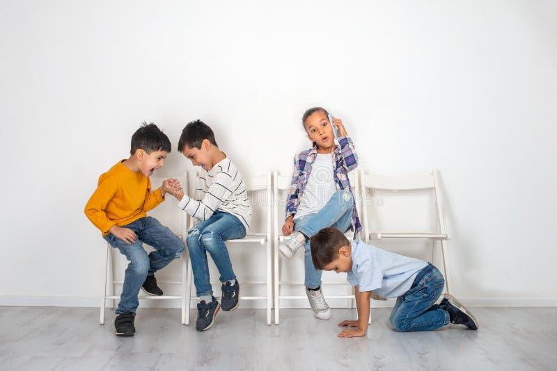 孩子、女孩和三个男孩情感演播室射击坐椅子等待 更老的男孩演奏armwrestling,更加年轻的男孩 库存图片