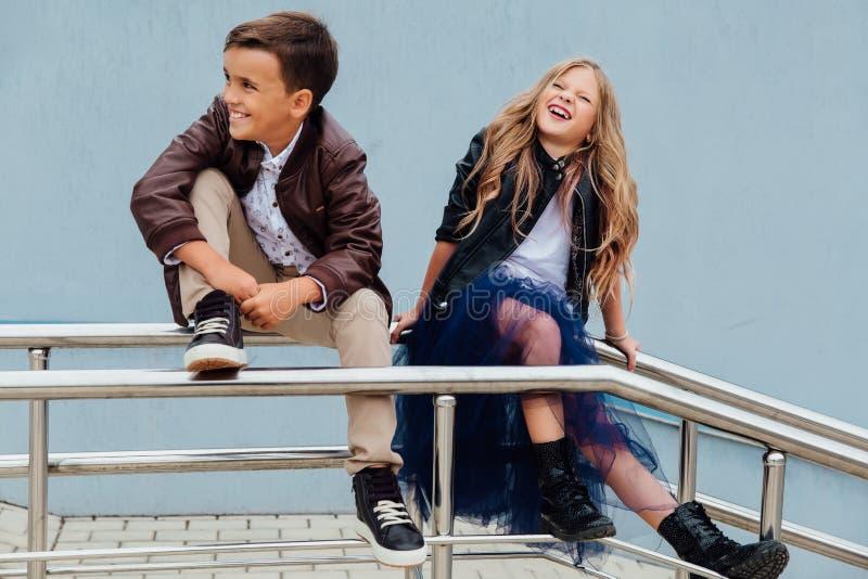 孩子、男孩和女孩坐在公园朋友的栏杆 友谊的概念 图库摄影