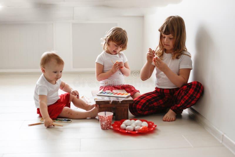 孩子三个兄弟姐妹油漆鸡蛋,复活节 免版税图库摄影