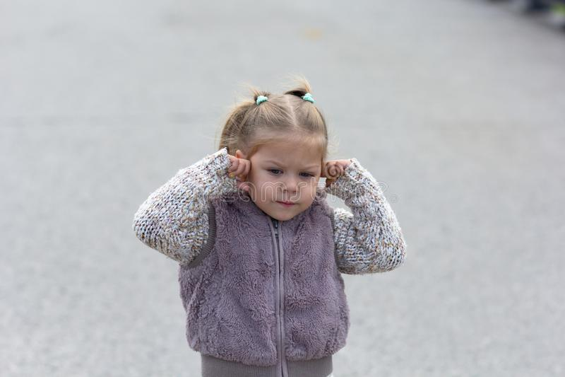 孩子不要听见什么关闭她的耳朵 免版税库存图片