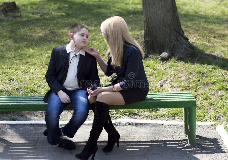 孩子与母亲谈话在公园 免版税库存照片