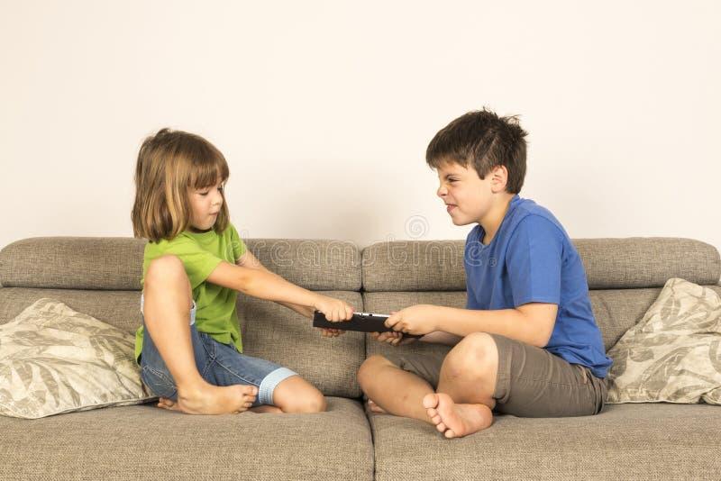 孩子为赞成使用而辩论与一种数字式片剂 库存图片