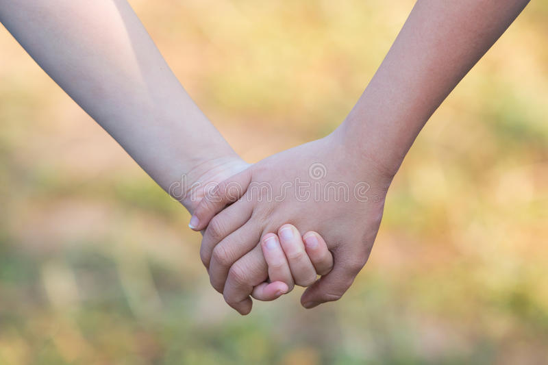 孩子举行为支持和友谊的`手,弄脏绿草 库存图片