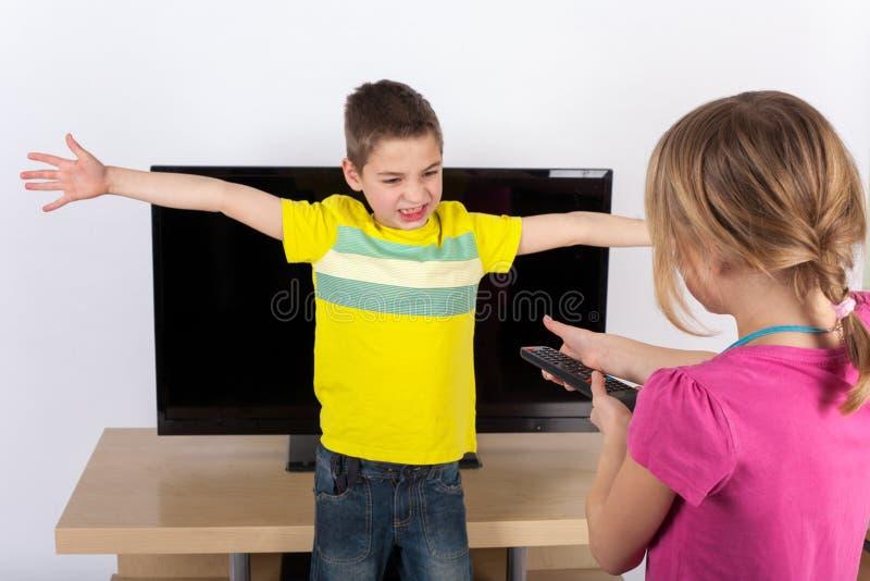 孩子争论关于电视 免版税库存照片