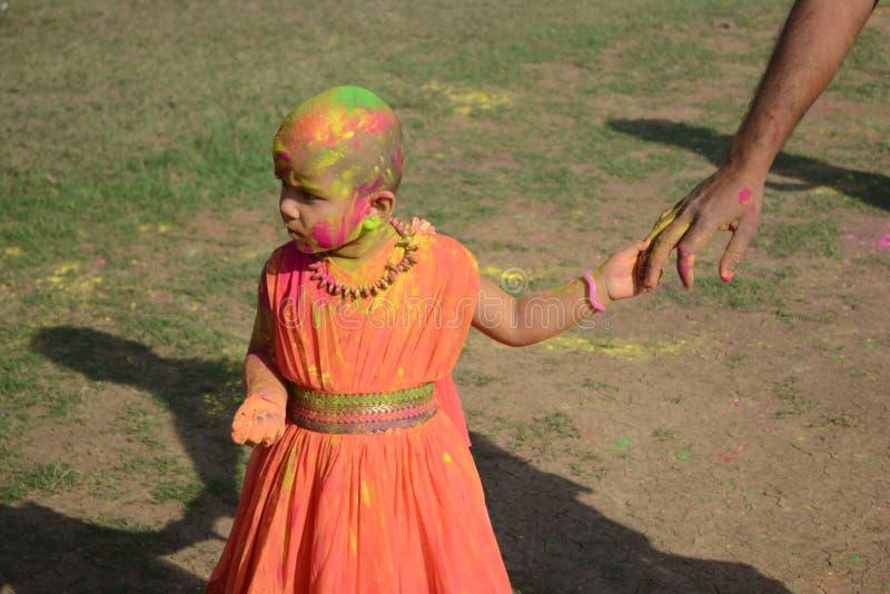 孩子享用与她的父亲,印度的颜色节日的Holi 免版税库存照片