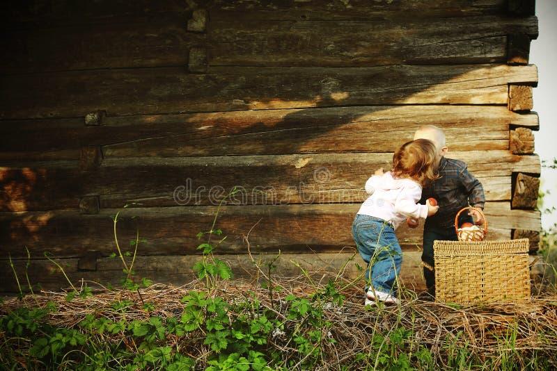 孩子亲吻木房子春天篮子鸡蛋 免版税库存照片