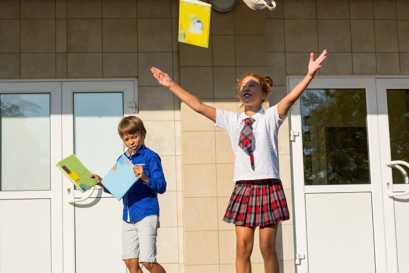 孩子从学校愉快地跑并且在en以后投掷书 图库摄影