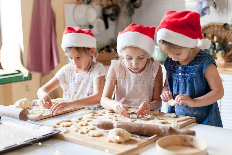 孩子们在家厨房做圣诞姜饼饼干 戴着圣诞帽的可爱孩子正在做节日晚餐 免版税库存图片