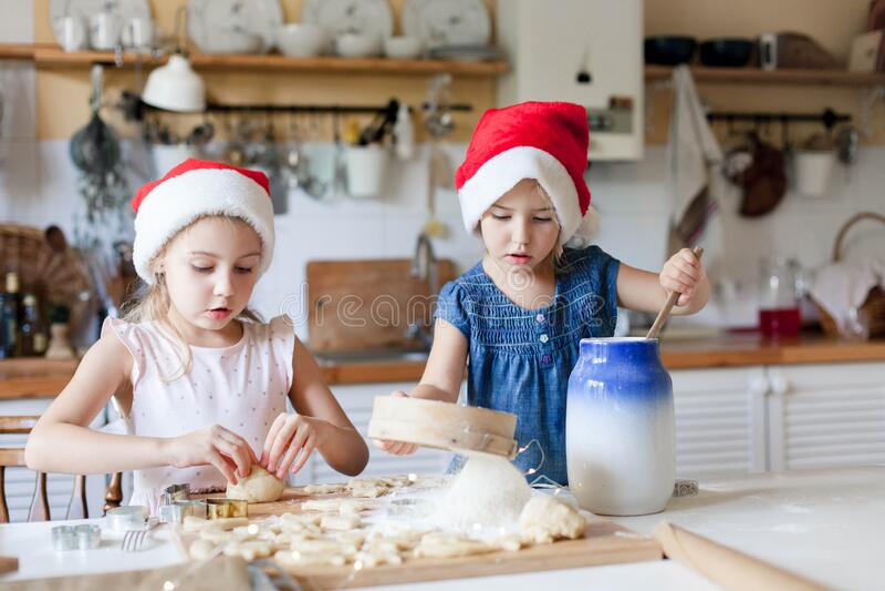 孩子们在舒适的家庭厨房里做圣诞饼干 可爱的孩子为家人准备假日食物 免版税库存照片