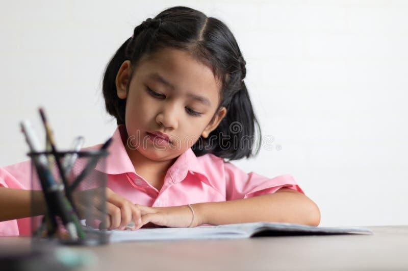 孩子使用一个橡皮擦删除词 免版税库存照片