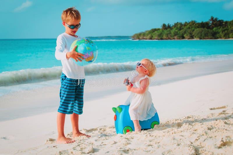 孩子使用与在海滩的地球和玩具飞机,旅行概念 免版税库存照片