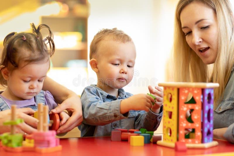 孩子使用与形状和五颜六色的木难题在montessori教室 免版税库存图片