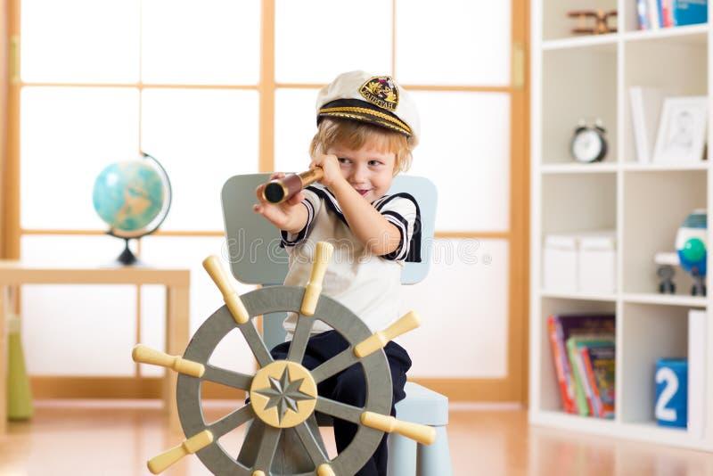 孩子假装是水手 哄骗看通过望远镜的男孩在家使用 库存图片