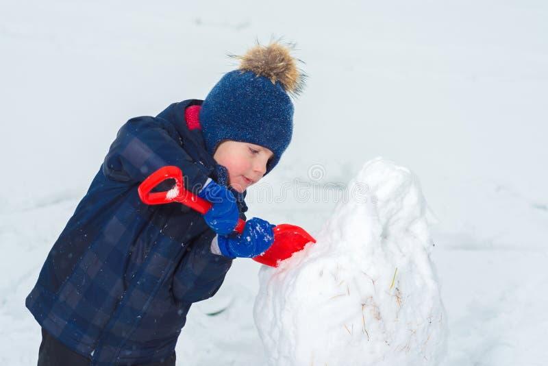 孩子做与铁锹的一个在雪的雪人和戏剧 免版税图库摄影