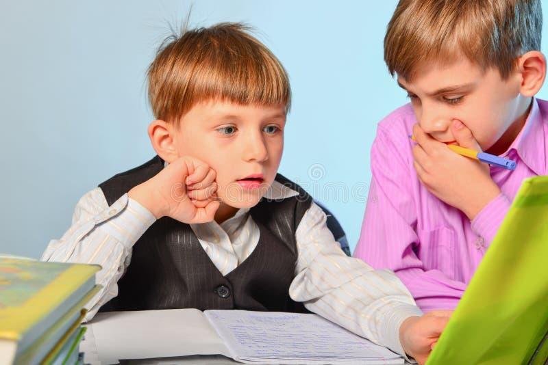 孩子做他们的家庭作业,解决问题和准备好学校 图库摄影