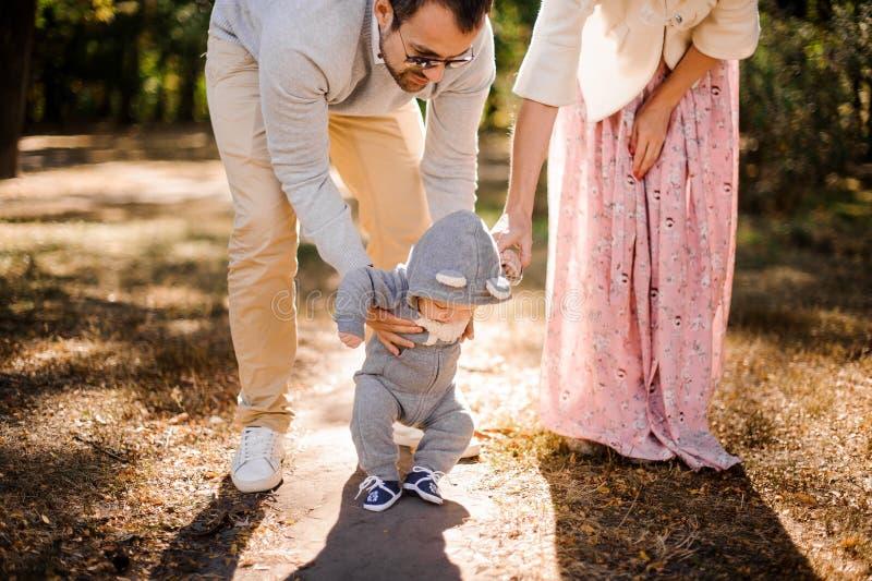 孩子做他的第一步,握手爸爸和母亲 免版税库存照片