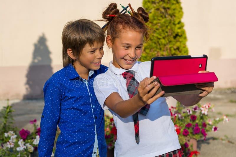 孩子做在片剂和微笑的selfie 图库摄影