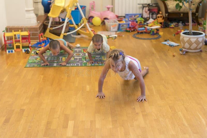 孩子做锻炼 一种健康生活方式的概念 Children& x27; s体育 孩子从地板被推挤 复制 免版税库存图片