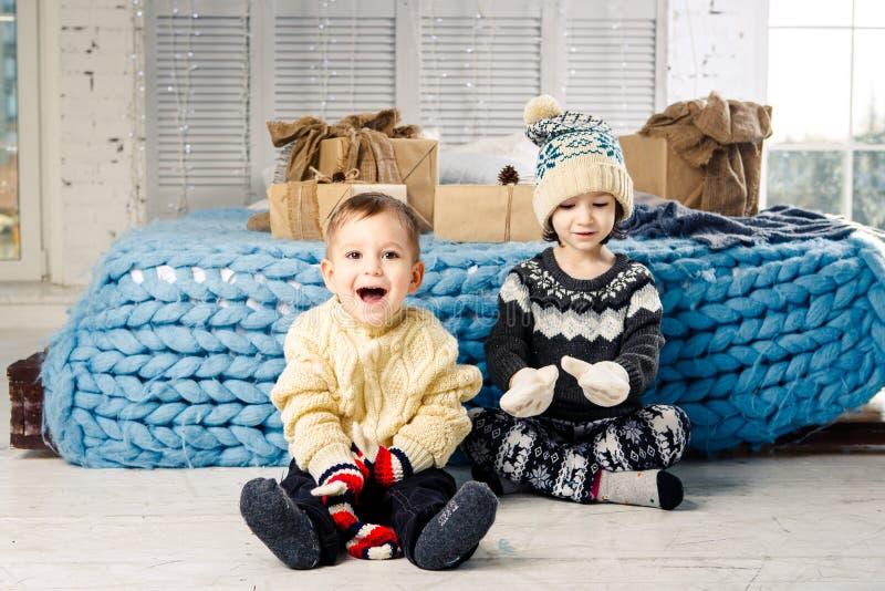 孩子兄弟和姐妹坐地板在卧室在与礼物的床附近在圣诞节装饰背景在晴朗的da的 库存照片