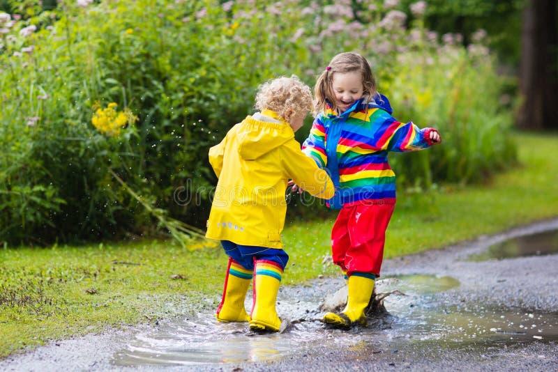 孩子充当雨和水坑在秋天 免版税图库摄影