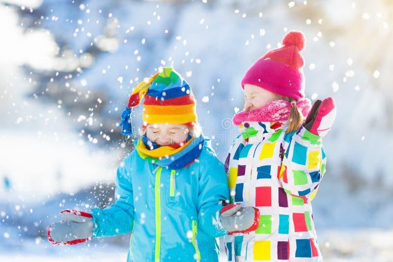 孩子冬天雪球战斗 在雪的儿童游戏 库存照片