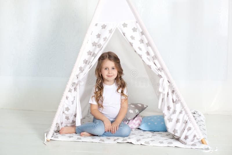 孩子准备上床 宜人的时间在舒适卧室 女孩在与五颜六色的枕头的一个圆锥形帐蓬坐在她的屋子里 Decorati 免版税图库摄影
