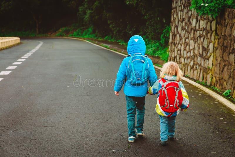 孩子去教育-在路的兄弟和姐妹步行 库存图片