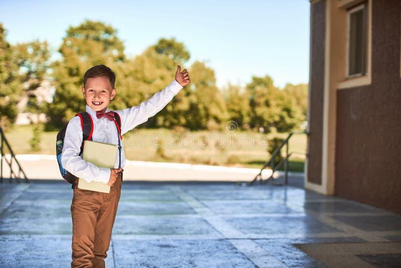 孩子去教育 男孩男小学生去早晨教育 有一个公文包的愉快的孩子在他的和课本  图库摄影