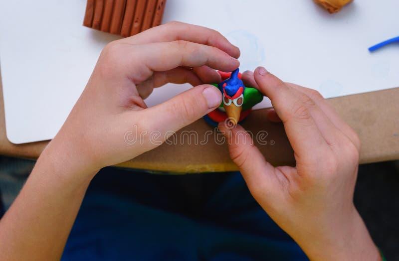 孩子参与彩色塑泥坐在儿童` s桌里的塑造 库存照片