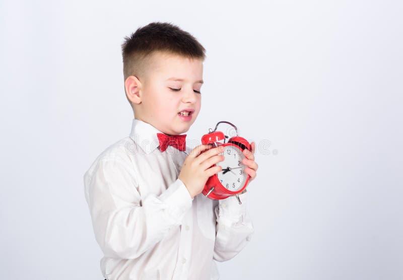 孩子可爱的男孩白色衬衫红色蝶形领结 开发自我训练 设定闹钟 儿童小男孩举行红色时钟 免版税库存图片