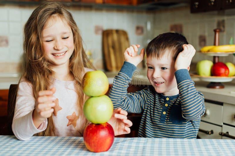 孩子吃苹果并且获得乐趣在厨房里在早晨 免版税图库摄影