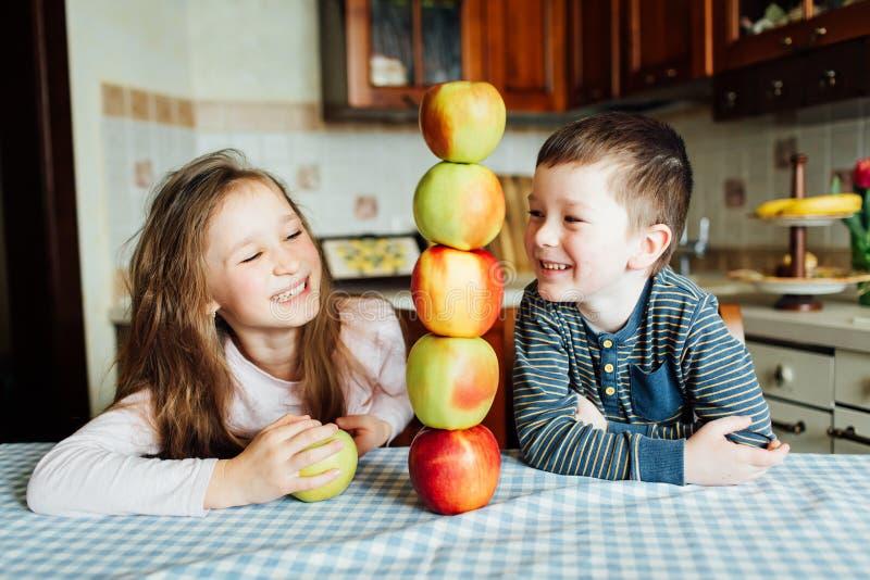 孩子吃苹果并且获得乐趣在厨房里在早晨 免版税库存图片