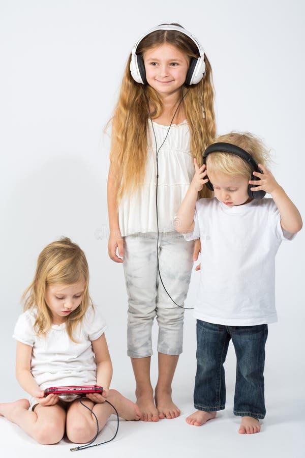孩子听到在耳机和女孩使用的音乐 免版税库存图片