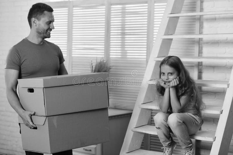 孩子和人移动或搬出 新的家和家庭观念 女儿和父亲拿着箱子并且打开或者包装 免版税库存图片