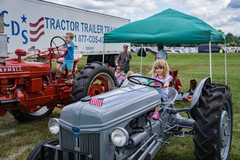 孩子和农用拖拉机 免版税库存图片