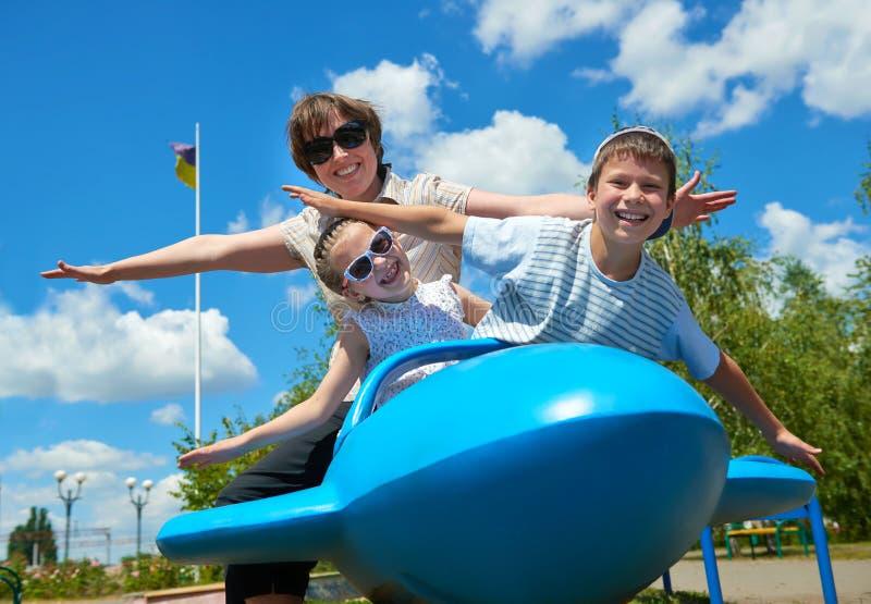 孩子和妇女在蓝色飞机吸引力飞行在公园,获得愉快的家庭乐趣,暑假概念 免版税库存图片